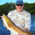 Tis is a fisherman holding a redfish caught during his tampa fishing trip