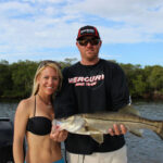 male and female holding a snook