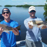 guys holding caught redfish