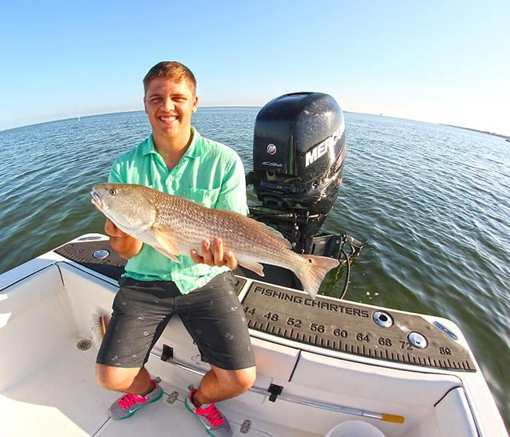 fisherman with a large caught redfish