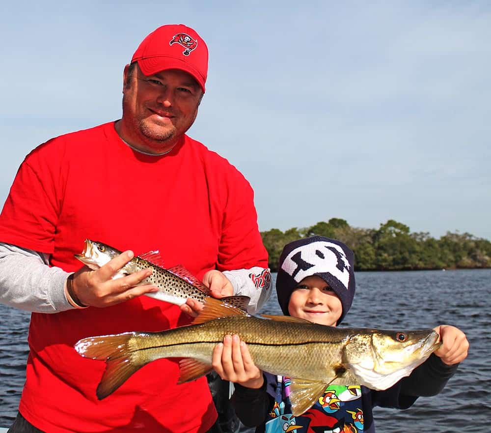 father and son holding two fish