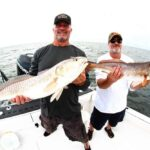 fishing team holding large redfish