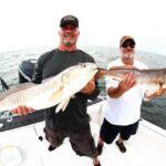 fishing team holding large redfish