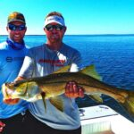 two fisherman holding a snook